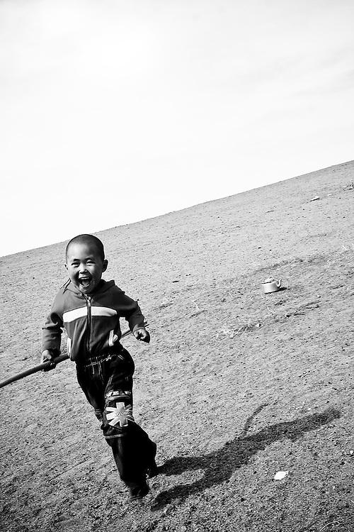 A young boy runs in rural Mongolia.