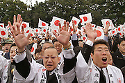 """These are well-wishers giving the traditional """"banzai"""" cheer to Japanese Emperor Akihito and family during the Emperor's annual New Year's greetings for 2006. Most who attended waited for hours in the cold and rain before getting a glimpse of the imperial family in central Tokyo. According to the the Imperial Household Agency, about 50,200 people showed up to see the Emperor make seven different appearances from the glass covered balcony of the Chowa Den wing of the Imperial Palace. This view is from the first appearance, and those shouting banzai were steeped in nationalistic pride. When addressing the visitors, the Emperor said """"I am truly pleased to celebrate the New Year with you,"""" and """"I wish for the happiness of people in our country and peace in the world."""" The 72 year old Emperor was accompanied by family members including Empress Michiko, Crown Prince Naruhito and Crown Princess Masako who has been marred in controversy due to stress related illness. The imperial family appeared three times in the morning and four times in the afternoon on January 2, 2006."""