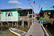 Kampung Buli Sim Sim, stilt village in Sandakan, Malaysian Borneo.  Houses are typical Asian water village construction. The entire village is served by water from a narrow pipe that runs along the top of the wooden plank jetty.  Toilets flush directly into the bay beneath the houses. Jetty 23 is considered safe for tourists to visit, but other stilt villages in Sandakan are extremely dangerous.  The government is attempting to shut down some of the most crime ridden of these villages.
