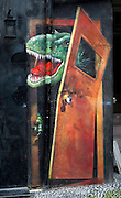 Dafen, China<br /> Dafen Art Village.Street art in the village of T-rex breaking down a door.<br /> Chinese: 大芬; pinyin: Dàfēn is a suburb of Buji, Longgang, Shenzhen in Guangdong province, China.<br /> Pic Jayne Russell +852 97578607.<br /> Date-08.05.13<br /> 8th May 2013