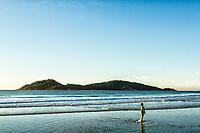 Garoto andando na água na Praia do Campeche ao amanhecer, e Ilha do Campeche ao fundo. Florianópolis, Santa Catarina, Brasil. / Boy walking in the water at Campeche Beach at dawn, and Campeche Island in the background. Florianopolis, Santa Catarina, Brazil.