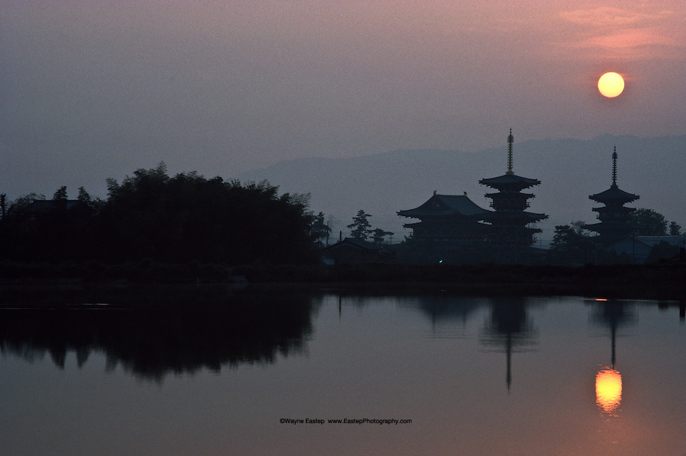 Pagodas at the Hosso Buddhist Yakushiji Temple point to the sun rising over Nara, the city that became Japan's first permanent capital in A.D. 710. The three-storied pagodas were built with mokoshi, inter-story pent roofs.