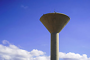 Concrete water tower on blue sky background