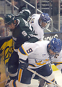 Michigan State's Matt Schepke (center) gets pinned along the boards by Lake Superior State's Josh Sim (center) and Troy Schwab (right) during the second period of the Spartans 4 to 2 loss to the Lake Superior State Lakers in Sault Ste. Marie.