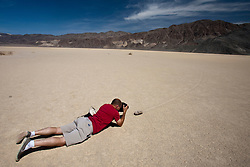 Adult male photographer taking pictures of a moving rock, Racetrack Playa, Death Valley National Park, California, United States of America