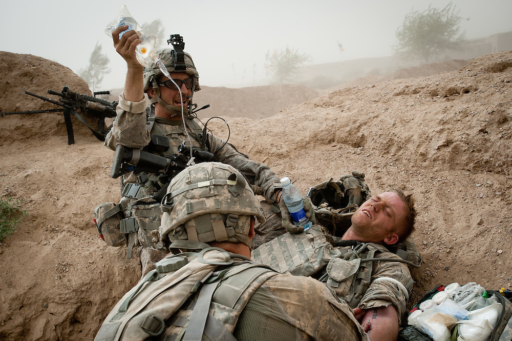 Sergeant Dennis Johnson, left, holds an IV bag while a medic gives aid to an injured soldier.