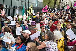 London, UK. 23rd April 2019. Climate change activists from Extinction Rebellion in Parliament Square hold up letters to their Members of Parliament requesting meetings to discuss the issue of climate change. Activists tried to deliver their letters to Parliament, but all but ten were prevented from doing so by the Metropolitan Police.