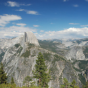Yosemite National Park's most well-know feature is Half Dome, which stands at an altitude of 8,836 feet and 4,737 feet above the valley floor. As the rock was exposed, weathering and exfoliation of shell-like outer layers of the rock shaped the dome portion of the rock to its current shape. The summit is attainable as a day hike in the summer, if you have the stamina to undertake a 17-mile roundtrip hike with 5000 feet of elevation gain from the valley floor.  Nevada and Vernal Falls are visible on the left and are accessible only by foot.  A mountain stream formed by snow melt forms Nevada Falls, 594 feet (181 m), which then flows down to form Vernal Falls, 240 feet (73 m).  The stream eventually flows into the Merced River.