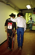 "14 DECEMBER 2002 - LAS VEGAS. NEVADA. USA: Jesse Bail, a bull rider from Camp Crook, SD, talks to Mike Rich, a medic with the Justin Sports Medicine Team, after being thrown from a bucking bull at the National Finals Rodeo in Las Vegas, NV, Dec 14, 2002. The NFR is the ""super bowl"" of rodeo and draws hundreds of thousands of rodeo fans to Las Vegas for ten days every December. The rodeo is held at the Thomas and Mack center, which sells out for all ten performances. Other cowboy and western themed events take place around Las Vegas.  PHOTO BY JACK KURTZ"
