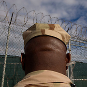 """A camp guard outside Camp 4 at the detention facility in Guantanamo Bay, Cuba. Camp 4 is a communal style camp where more compliant detainees live in small groups and have access to a more open air environment. Approximately 250 """"unlawful enemy combatants"""" captured since the September 11, attacks on the United States continue to be held at the detention facility.(Image reviewed by military official prior to transmission)."""