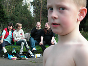 Kid staring into the camera, while a group of women on a bench are in fits of laughter in the background, UK, 2000's