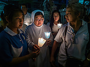25 MARCH 2016 - BANGKOK, THAILAND: A Catholic nun leads parishioners in a candle light vigil during Good Friday observances at Santa Cruz Church in Bangkok. Santa Cruz was one of the first Catholic churches established in Bangkok. It was built in the late 1700s by Portuguese soldiers allied with King Taksin the Great in his battles against the Burmese who invaded Thailand (then Siam). There are about 300,000 Catholics in Thailand, in 10 dioceses with 436 parishes. Good Friday marks the day Jesus Christ was crucified by the Romans and is one of the most important days in Catholicism and Christianity.      PHOTO BY JACK KURTZ