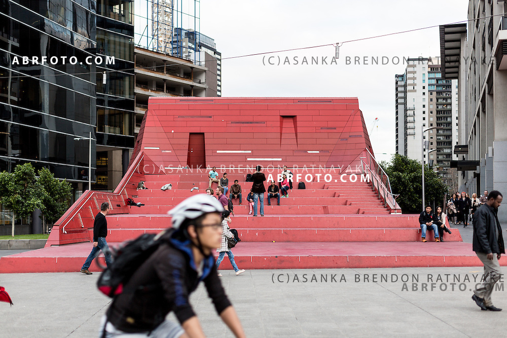 People sit on the red post modern amphitheatre at as pedestrians walk & ride by at Queensbridge Square Melbourne Victoria Australia