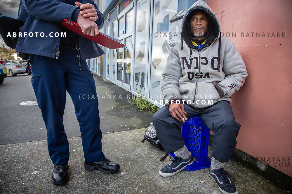 Joseph Takairangi sits outside shops in Henderson as he is issued a trespass notice from the Henderson community  constable on the 7th of June 2018. Joseph Takairangi has been warned previously about loitering around the Henderson shops. The issuing officer has worked with a number of the homeless in the area and responds often to complaints from local shop owners. Asanka Brendon Ratnayake for The New York Times.