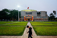 A young Vietnamese man walks along the grounds of the Ho Chi Minh Mausoleum in Hanoi, Vietnam, with the new Parliament building in the background.