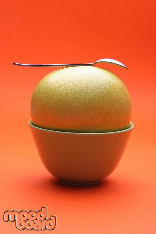Grapefruit in bowl on orange background