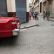 Cubans manage their daily life wether waiting for overcrowded busses or doubling up on old classic cars and motorcycles or walking everywhere. Locals and tourist walk and window shop in La Habana Vieja. <br /> Photography by Jose More