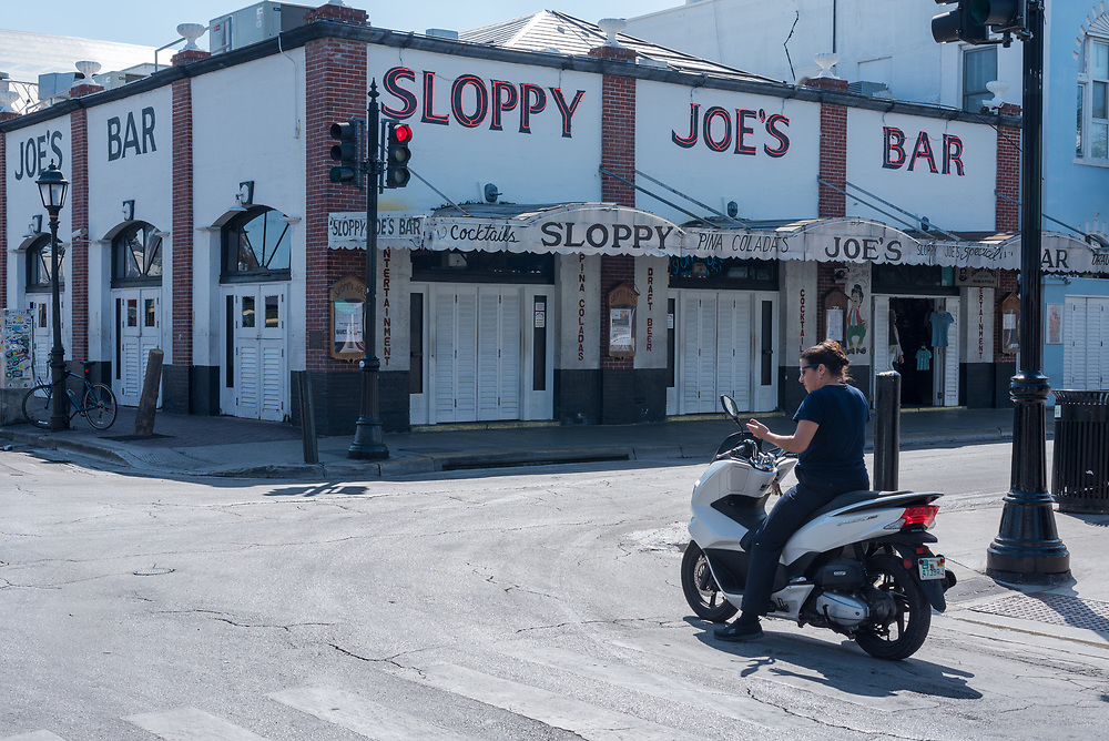 Key West, Florida--April 29, 2018.  Woman on motorbike outside the famous Sloppy Joe's Bar in Key West, near the original location where Hemmingway used to hang out. Editorial Use Only.