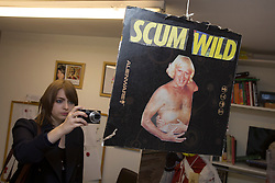 © licensed to London News Pictures. London, UK 24/10/2012. A spectator taking pictures of an artwork which made of newspaper cuttings at 'Jimmy Savile is innocent' exhibition at Bread and Butter Gallery in Islington. Photo credit: Tolga Akmen/LNP