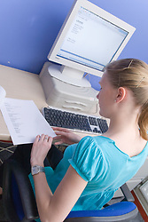 Teenaged girl on work experience placement from school doing typing up some documents in the work place,