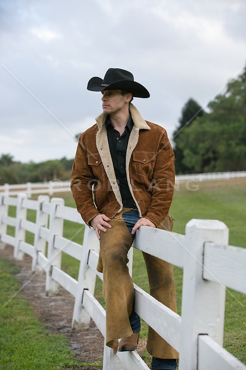 rugged and handsome cowboy sitting on a fence