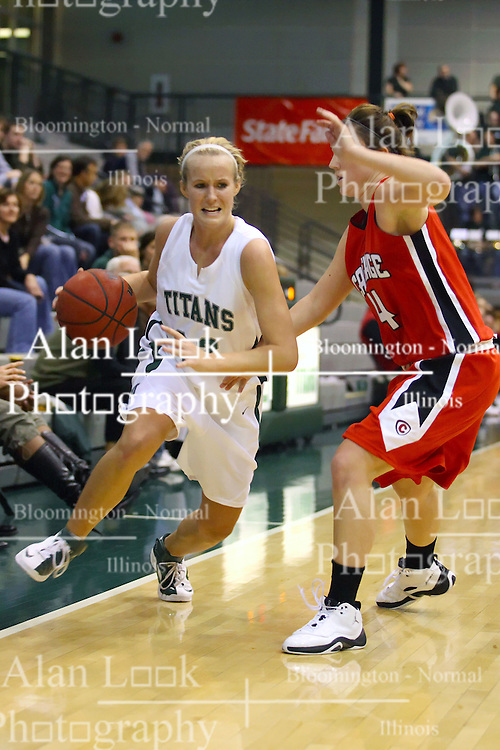 10 January 2009: Hope Schulte stays just inbounds as she drives in against Drewann Pancratz. The Illinois Wesleyan Titans, ranked #1 in the latest USA Today/ESPN poll, take down the Lady Reds of Carthage and remain undefeated,  2-0 in the CCIW and over all to 12-0. This is the first time in the history of the Lady Titans Basketball they have been ranked #1 The Titans and Lady Reds played in the Shirk Center on the Illinois Wesleyan Campus in Bloomington Illinois.