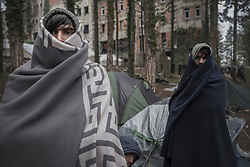 November 3, 2018 - Bihac, Bosnia and Herzegovina - Two men wrapped in blankets as they stand outside a camp and building. In the city on the border with Croatia there are hundreds of migrants of Pakistani and Afghan origin who try to cross the border often clashing with the Croatian police. Many of the migrants are injured and deprived of their cell phone by the Croatian police. They live in a park and in several abandoned buildings. Every day the migrants wash themselfe and the clothes in the near river named Una. (Credit Image: © Danilo Balducci/ZUMA Wire)