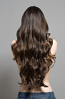 Woman with long brown wavy hair rear view