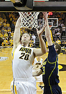 February 19 2011: Iowa Hawkeyes forward Andrew Brommer (20) puts up a shot as Michigan Wolverines forward Evan Smotrycz (23) defends during the first half of an NCAA college basketball game at Carver-Hawkeye Arena in Iowa City, Iowa on February 19, 2011. Michigan defeated Iowa 75-72 in overtime.