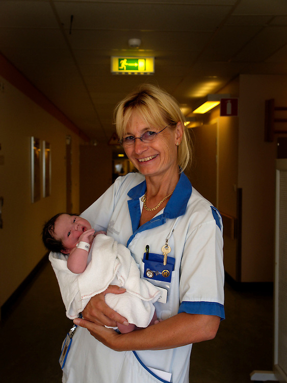 Marianne Gertzell - department boss. The Midwife in chief in Uppsala holds a 5 hour old girl. who has yet to be named. She is just one of the aproximately 10 children that will be born there that day.