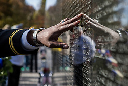 A United States Military Officer points out the name of a family member to his wife and children on the Vietnam Veterans Memorial on the National Mall in Washington, D.C. on Veterans Day, November 11th, 2017.