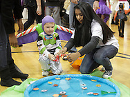 Middletown, New York - A volunteer helps a young boy wearing a costume play a fishing game at the Family Fall Festival at the Middletown YMCA on Oct. 23, 2010. ©Tom Bushey / The Image Works
