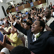 Mount Vernon, NY / 2008 - Reverend W. Darin Moore, center, participates in a pastoral anniversary revival with his congregation at the Greater Centennial AME Zion Church in Mount Vernon June 11, 2008. Moore grew up attending the AMZ Zion Church and now he's celebrating his 15th year as pastor. He has helped to grow the church from 800 members to 5,000, making it one of the largest churches in the national denomination. This is particularly unusual because in the AME Zion denomination, which is historically Methodist, pastors are generally transferred every few years by the bishop who oversees each jurisdiction. In Moore's case, church officials are allowing him to remain because Greater Centennial plays such an important role in the city of Mount Vernon.  ( Mike Roy / The Journal News )