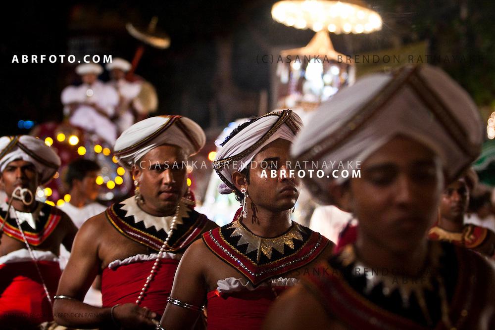 Kandyan themed drummers walk towards the Gangaramaya Temple.