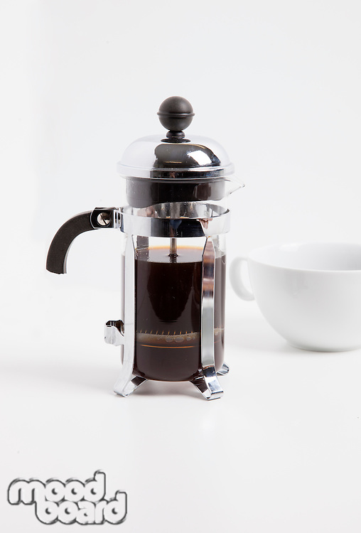 Coffee maker and cup against white background