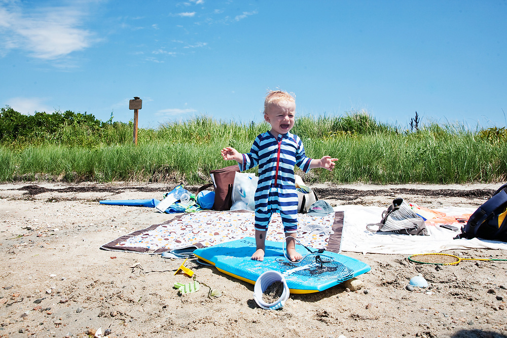 1 year old baby boy crying on beach on surfboard