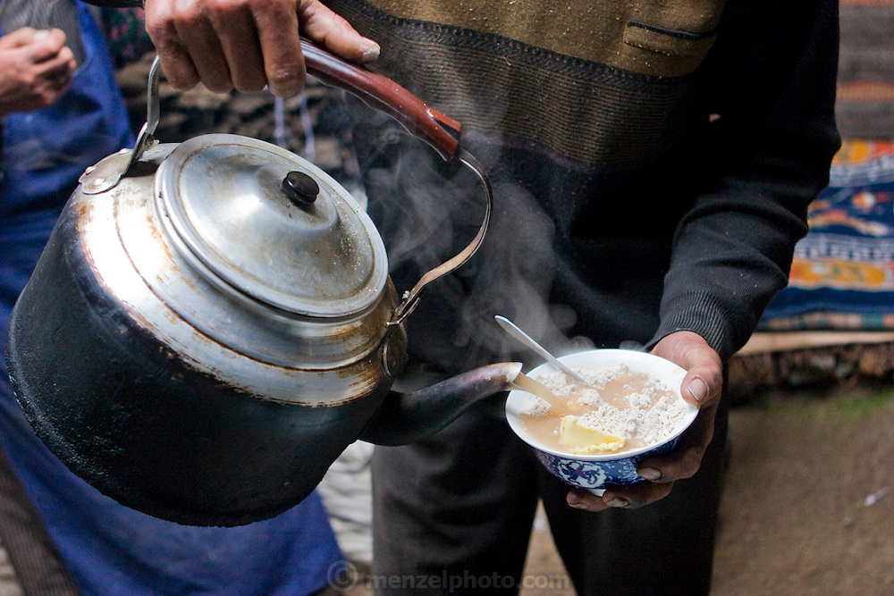 Nomadic herder Karsal pours butter tea onto his breakfast tsampa in his tent on the Tibetan Plateau.  (Karsal is featured in the book What I Eat: Around the World in 80 Diets.)