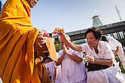 20 OCTOBER 2012 - BANGKOK, THAILAND: Women give donations of food, juice and cash to Buddhist monks at an alms giving ceremony in Bangkok. More than 2,600 Buddhist Monks from across Bangkok and thousands of devout Thai Buddhists attended the mass alms giving ceremony in Benjasiri Park in Bangkok Saturday morning. The ceremony was to raise food and cash donations for Buddhist temples in Thailand's violence plagued southern provinces. Because of an ongoing long running insurgency by Muslim separatists many Buddhist monks in Pattani, Narathiwat and Yala, Thailand's three Muslim majority provinces, can't leave their temples without military escorts. Monks have been targeted by Muslim extremists because, in the view of the extremists, they represent the Thai state.        PHOTO BY JACK KURTZ