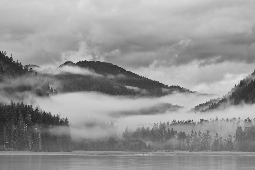Low hanging clouds and fog shroud the mountains of Admiralty Island National Monument near the tidal flats of Windfall Harbor in the Inside Passage of Southeast Alaska.  Tongass National Forest. Summer.  Morning.