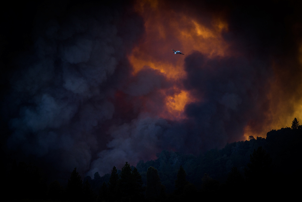 A spotter plane flies past the Sand Fire as it burns near Plymouth, California, July 26, 2014. <br /> The Sand Fire destroyed 20 homes and burned more than 4,200 acres near the town of Plymouth.
