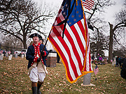 14 DECEMBER 2019 - DES MOINES, IOWA: RICK HICKMAN, wearing uniform of the Revolutionary War Continental Army, with an American flag at the Christmas wreath laying ceremony in Woodlands Cemetery. Volunteers working with Wreaths Across America placed Christmas wreaths on the headstones of more than 600 US military veterans in Woodland Cemetery in Des Moines. The cemetery, one of the first in Des Moines, has the graves of veterans going back to the War of 1812.PHOTO BY JACK KURTZ