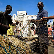 "Fishermen clean their nets after returning from sea in Cape Coast, roughly 120km west of Ghana's capital Accra on Thursday April 9, 2009. ""Local jobs are collapsing"" says the Ministry of Fisheries' Isiah Amoukouandoh. ""It's a difficult balance for the government because foreign trawlers contribute to government funds. If the trawlers stuck to regulations, there would be less of a problem. But they are fishing in the waters reserved for the local fishermen, stealing their fish."""