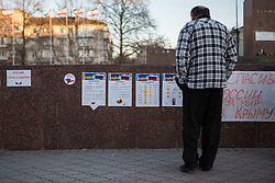 Crimea one day before the referendum. A crimean looks at a propaganda banner showing the benefits of joining Russia. Simferopol, . Saturday, 15th March 2014. Picture by Daniel Leal-Olivas / i-Images