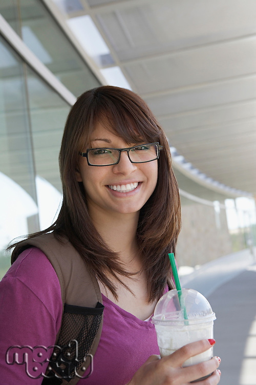 Female student holding drink at school, smiling, portrait