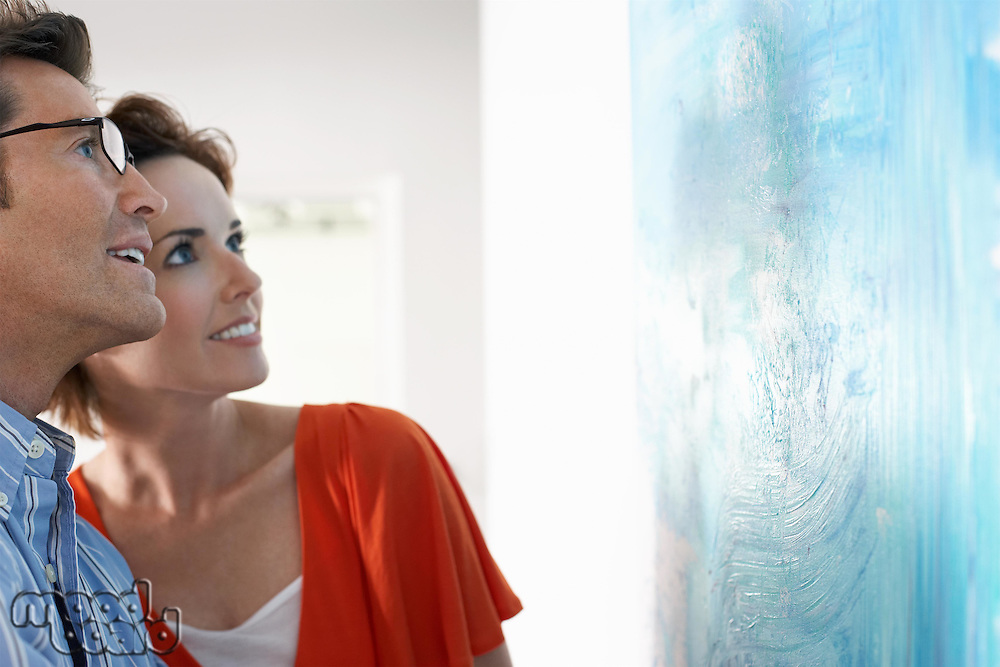 Couple looking at modern art painting in gallery