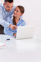 Businessman and businesswoman working together on a computer
