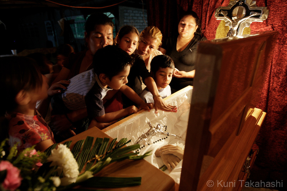 Children of Mariana de la Torre touch a casket of their mother during the vigil in Apatzingan, Mexico on April 8, 2009. (Photo by Kuni Takahashi)