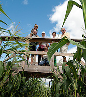 Brian, Ty,  June, Drew, Jennifer and Bruce Anderson try using the higher vantage point from one of bridges within the Beans and Greens corn maze to help determine which direction they should go as they work their way through the corn stalks Sunday afternoon.   (Karen Bobotas/for the Laconia Daily Sun)