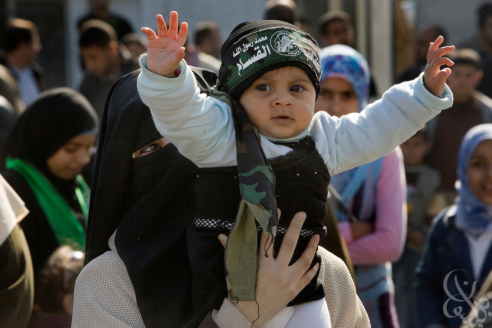 "A Palestinian woman holds up her child at a ""Victory"" parade thrown by militant Palestinian political group HAMAS January 20, 2009 in Gaza City. Several thousand marchers celebrated what HAMAS called the defeat of Israel during the recent 21 day offensive by Israeli forces against HAMAS fighters. During the operation more than 1500 Palestinians were killed and more than 4000 homes destroyed in the narrow Gaza Strip..."