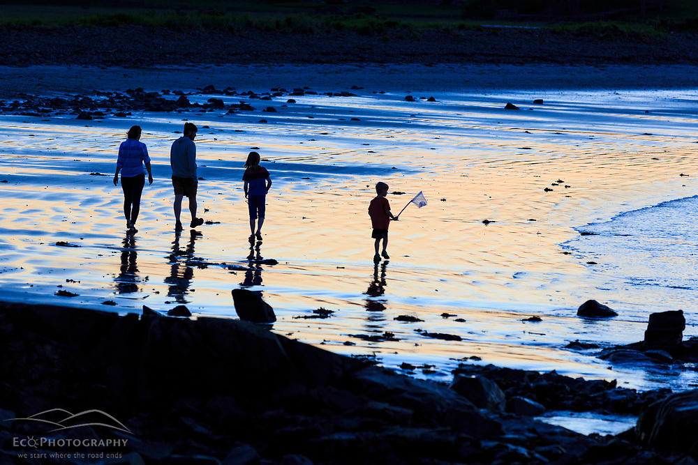 A couple and their kids walk on the sand after sunset at Seapoint Beach in Kittery, Maine.